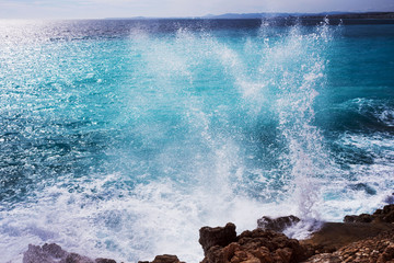 Beautiful turquoise sea, the mountains in the haze and the embankment of the Promenade des Anglais on a warm sunny day. Waves breaking on the rocks. Splashing water. Wall mural