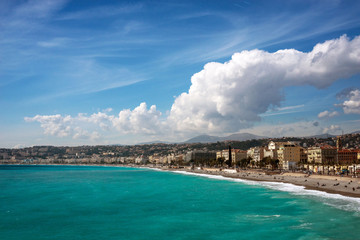 Tuinposter Algerije Nice, France, March 2019. Panorama. Azure sea, waves, English promenade and people resting. Rest and relaxation by the sea. On a sunny warm day, blue waves roll.