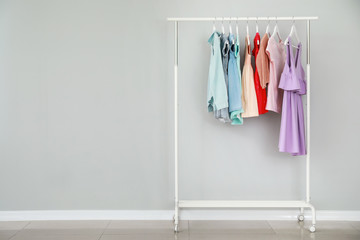 Rack with stylish children's clothes near light wall Wall mural