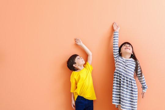 Cute little children measuring height near color wall