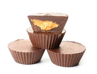 Tasty chocolate peanut butter cups on white background