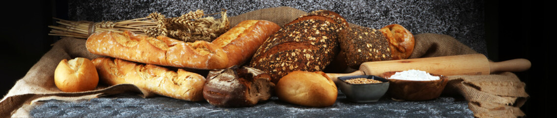 Assortment of baked bread and bread rolls on rustic grey bakery table background