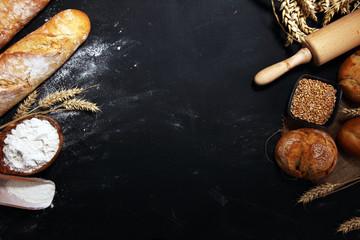 Foto op Canvas Bakkerij Assortment of baked bread and bread rolls on rustic black bakery table background