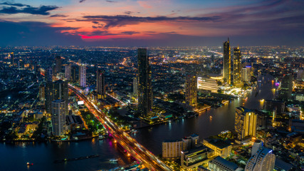 Fototapete - Aerial view of Bangkok skyline and skyscraper with BTS skytrain Bangkok downtown. Panorama of Sathorn and Silom business district Bangkok Thailand at sunset.