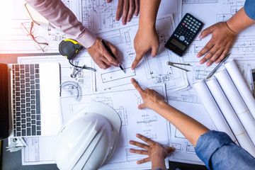 engineers pointing to building on blueprint and using laptop to drawing design building Project in office, construction concept. Engineer concept