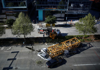 Seattle emergency personnel inspect the scene where part of a construction crane fell in a deadly accident on Mercer Street in Seattle