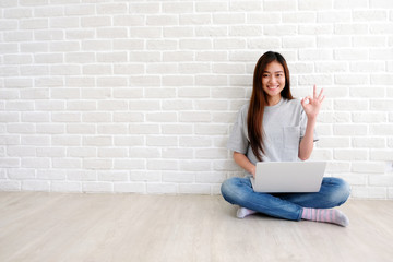 Young asian woman showing ok hand sign and smiling while working with laptop computer in white room with copy spce, people with positive gesture Wall mural