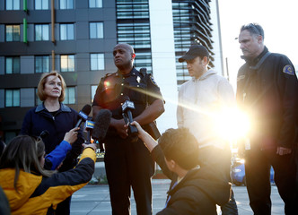 Seattle Mayor Durkan, left looks on as Seattle Police Assistant Chief Greening speaks near the scene where part of a construction crane fell in a deadly accident on Mercer Street in Seattle