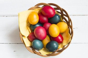 Traditional colored Easter eggs on wicker basket with wooden background