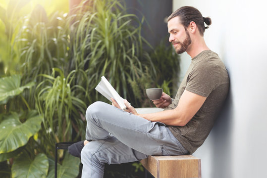 Relaxing Hipster man reading a book.