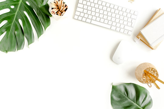 Flat lay home office desk. Female workspace with computer,  tropical palm leaves  Monstera, accessories on white background. Top view feminine background.