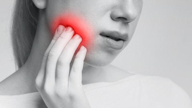 Young woman feeling toothache touching her cheek