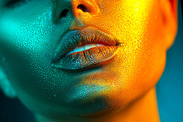 Wall Mural - Fashion model woman face in bright sparkles, colorful neon lights, beautiful sexy girl lips. Trendy glowing gold skin make-up. Glitter metallic shine makeup