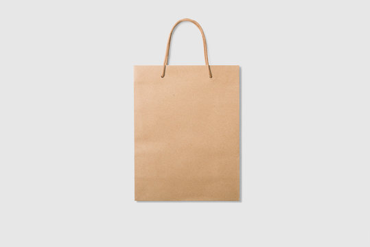 Mockup of a blank kraft paper shopping bag with handles on light grey background. High resolution.