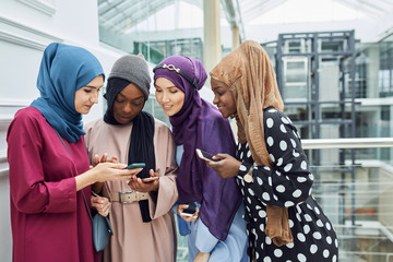 Asian Islamic women in bright hijabs sharing info from smartphone during their visit a seminar at education centre