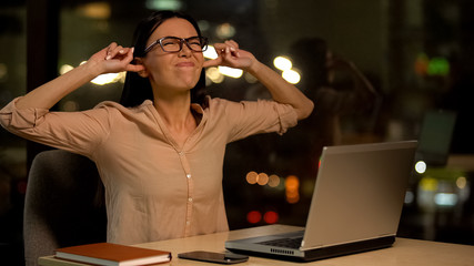 Woman covering ears, irritated with noise in office, nervous breakdown at work