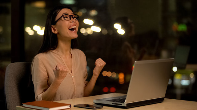 Excited female showing yes gesture sitting laptop, celebrating work success