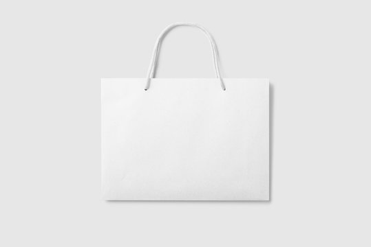Mockup of a blank white paper shopping bag with handles on light grey background. High resolution.