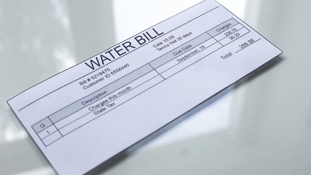 Water bill lying on table, payment for services, month expenses, tariff close up