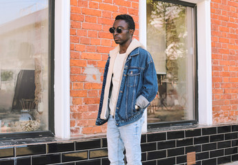 Wall Mural - Stylish african man wearing jeans jacket walking on city street over brick wall background