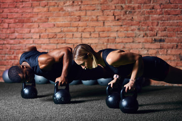 Dark-skinned man and white woman doing push ups on dumbbells. Cross-fit african trainer...