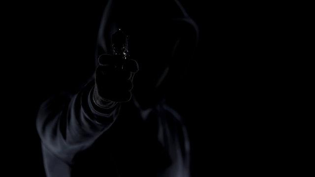 Cruel killer in black clothes aiming gun at camera, contract murder, shooting