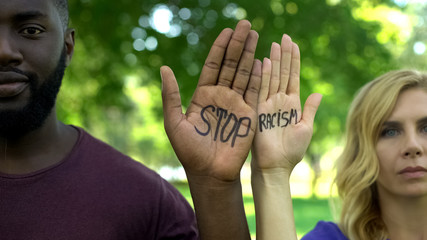 Afro-american man and caucasian woman showing palms with stop racism phrase