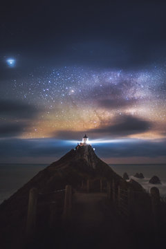 Milky Way arching over Cape Brett lighthouse on a hill in New Zealand