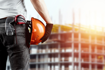 A builder, an architect holds in his hand a construction helmet against the background of a construction site, a tape measure. Concept architecture, construction, engineering, design, repair.