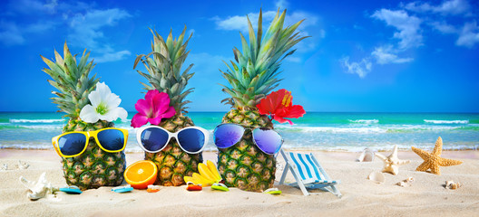 Attractive pineapples in stylish sunglasses on the sand beach against turquoise sea