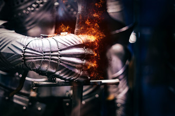 Close up of a Medieval steel armour with iron glove hand bursting with flames of fire, holding a giant sword
