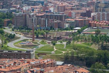 Blick vom Artxanda Park auf dem Etxebarria Park, wo ein Schornstein an die Industriegeschichte Bilbaos erinnert.