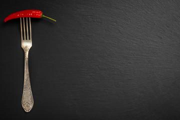 Fototapeta Papryczka chili nadziana na starym ozdobnym widelcu na czarnym tle kamienia łupkowego obraz