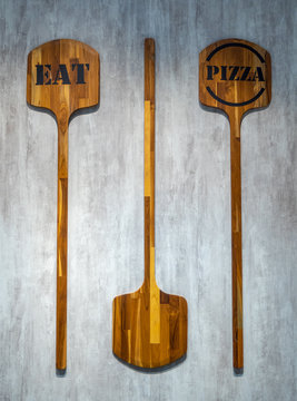 """Two pizza paddle with text """"eat"""" and """"pizza"""" hang on concrete wall for background"""