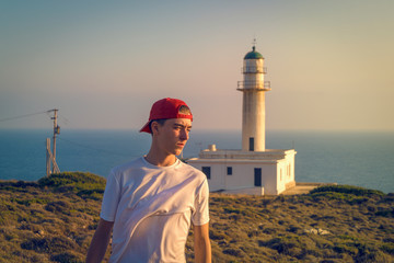 portrait of a young man in the evening sun, with a lighthouse in background