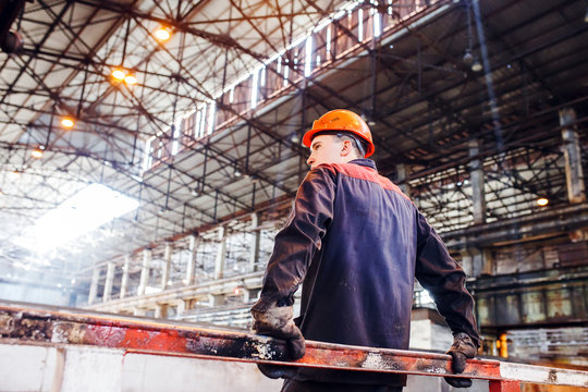 A man in a working form on the background of a metallurgical plant. tired of work worker.