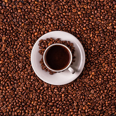 Cup of coffee on a background of coffee beans