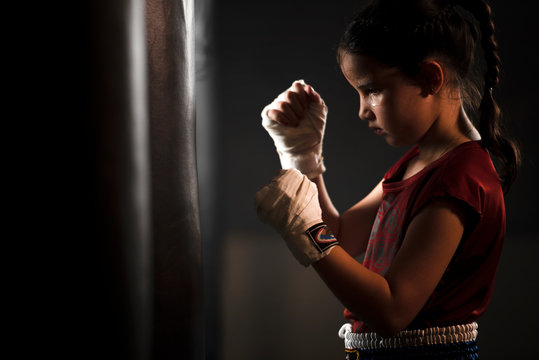 The female child in the boxing glove near the old punch bag The concept of martial arts and myself