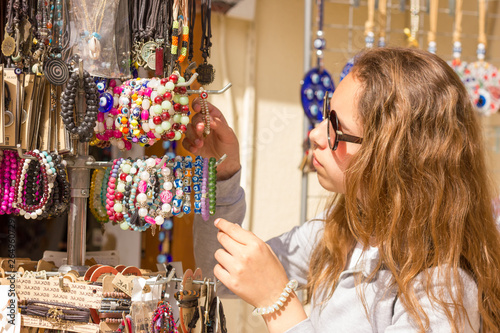 Young pretty girl chooses traditional jewelery at the