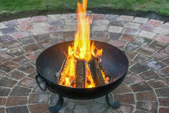 Geschmiedeter Feuerkorb mit wärmenden Feuer auf schönem Pflastersteinkreis im Garten