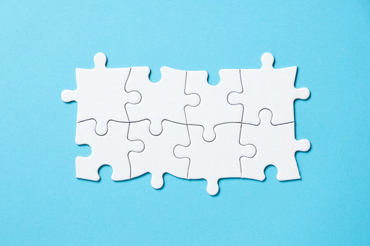 Eight pieces white jigsaw puzzle connected on blue background for business presentation