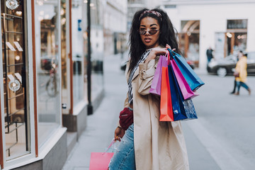 Attractive afro american woman with shopping bags standing on the street