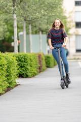 Junge Frau fährt mit e-Scooter in der Stadt