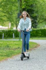 Junge Frau fährt mit e-Scooter in einem Park in der Stadt