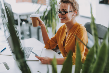 Smiling woman with cup of coffee and smartphone in the office