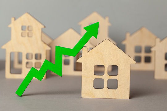 Up arrow and many houses. Growth in real estate prices market. Buying and selling house