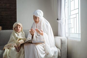 Keuken foto achterwand Bakkerij mother and kid reading quran together at home
