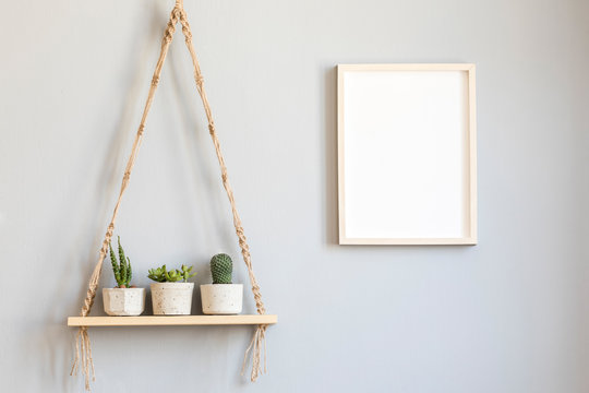 Stylish and minimalistic scandinavian interior with mock up poster frame and hanging wooden shelf with beautiful succulents in cement pots. Modern home decor. Gray background wall. Real photo.