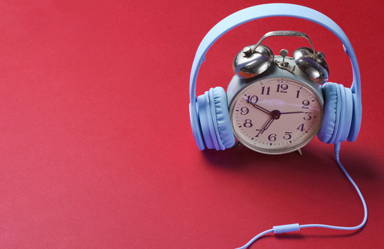 Retro alarm clock with wired headphones on red background.