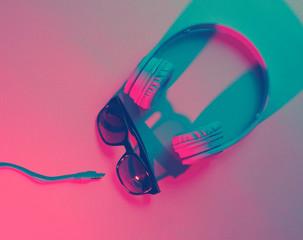 Sunglasses with headphones. Retro wave, blue pink neon light, ultraviolet. Top view, minimalism